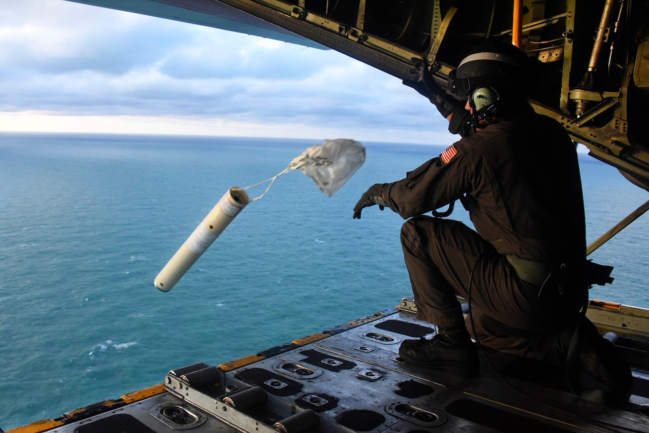 A Coast Guardsman tosses a cylindrical object out of the back of an open aircraft.