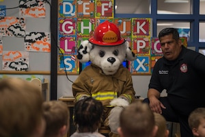 Sparky, the 97th Civil Engineer Squadron firehouse mascot and Roger Jara Jr., a fire inspector assigned to the 97th CES, talk to children at the Child Development Center about fire safety, Oct. 9, 2018 at Altus Air Force Base, Okla.