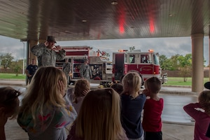 Firefighters assigned to the 97th Civil Engineer Squadron show off a firetruck to the children at the Child Development Center, Oct. 9, 2018 at Altus Air Force Base, Okla.