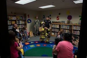 Firefighters assigned to the 97th Civil Engineer Squadron, teach children at the Altus Air Force Base Library the equipment they use during a fire, Oct. 9, 2018 at Altus AFB, Okla.