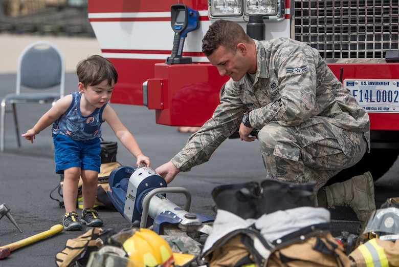 Airman 1st Class Casey Erdman, a firefighter in the 123rd Civil Engineer Squadron, demonstrates the use of hydraulic rescue tools to Ronan Daniels, son of the Kentucky Air National Guard's Benjamin Daniels, during the 123rd Airlift Wing's Family Day at the Kentucky Air National Guard Base in Louisville, Ky., Sept. 16, 2018. The event, which was sponsored by the Airman and Family Readiness Office and the Key Volunteer Group, featured a car show, a static-display C-130 Hercules aircraft and several other activities. (U.S. Air National Guard Photo by Staff Sgt. Joshua Horton)