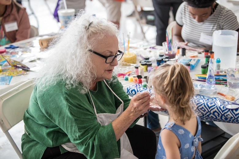 A volunteer paints a child's face during the 123rd Airlift Wing's Family Day at the Kentucky Air National Guard base in Louisville, Ky., on Sept. 16, 2018. The event, which was sponsored by the Airman and Family Readiness Office and the Key Volunteer Group, featured a car show, a static-display C-130 Hercules aircraft and several other activities. (U.S. Air National Guard photo by Master Sgt. Phil Speck)