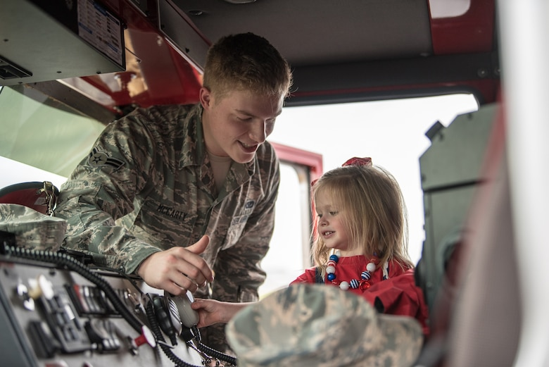 Airman 1st Class Benjamin McCarty, a firefighter assigned to the 123rd Civil Engineer Squadron, shows the unit's fire truck to Ruby Johnson, daughter of the Kentucky Air National Guard's Christopher Johnson, during Family Day at the Kentucky Air National Guard Base in Louisville, Ky., Sept. 16, 2018. The event, which was sponsored by the Airman and Family Readiness Office and the Key Volunteer Group, featured a car show, a static-display C-130 Hercules aircraft and several other activities. (U.S. Air National Guard photo by Master Sgt. Phil Speck)