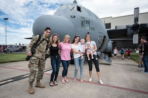 Family and friends pose in front of a 123rd Airlift Wing C-130 Hercules aircraft during Family Day at the Kentucky Air National Guard Base in Louisville, Ky., Sept. 16, 2018. The event, which drew a crowd of more than 1,000 people, featured lunch, games, a car show and numerous other activities. (U.S. Air National Guard photo by Master Sgt. Phil Speck)