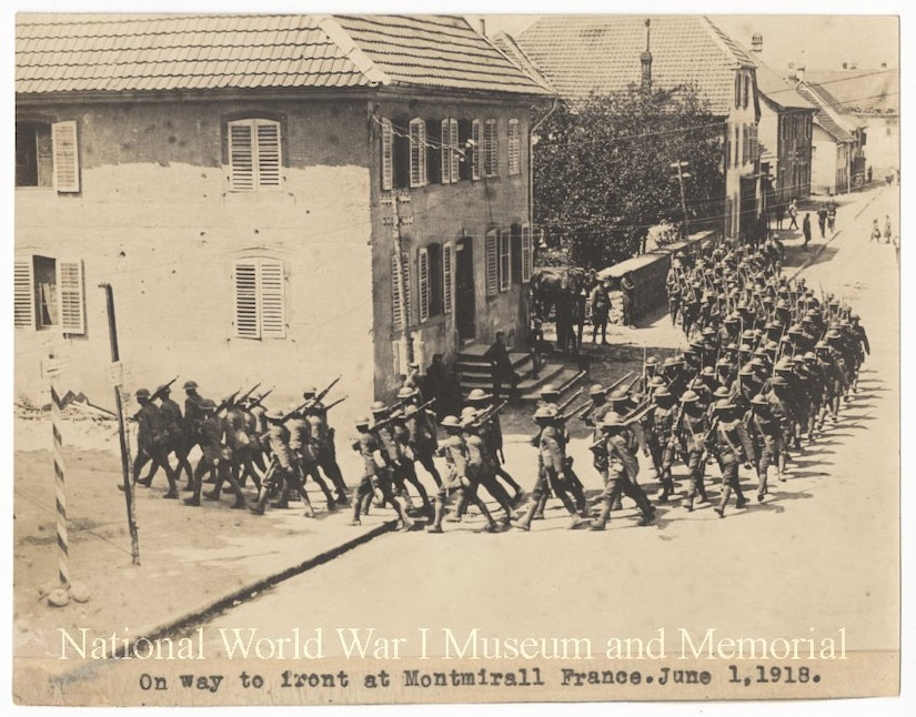 A group of American troops march through a town in World War l.