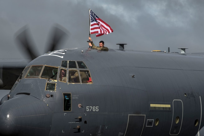 Capt. David Schmitt, 71st Rescue Squadron (RQS) HC-130J combat systems officer, waves a flag out of an HC-130J Combat King II during a redeployment ceremony, Oct. 9, 2018, at Moody Air Force Base, Ga. The 71st RQS maintains combat-ready status and provides deployable personnel recovery forces to theater commanders for contingency and crisis response operations worldwide. (U.S. Air Force photo by Airman Taryn Butler)