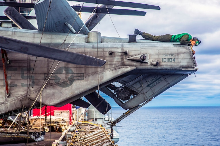 A Marine lays on top of the end of an aircraft clearing rust, over the open ocean.