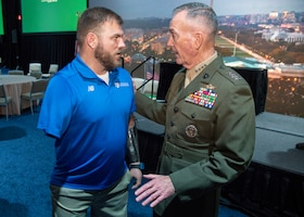 Marine Corps Gen. Joe Dunford, chairman of the Joint Chiefs of Staff, speaks to retired Army Staff Sgt. Travis Mills, Founder of the Travis Mills Foundation, during the New England Council Annual Dinner at the Seaport Hotel and World Trade Center in Boston.