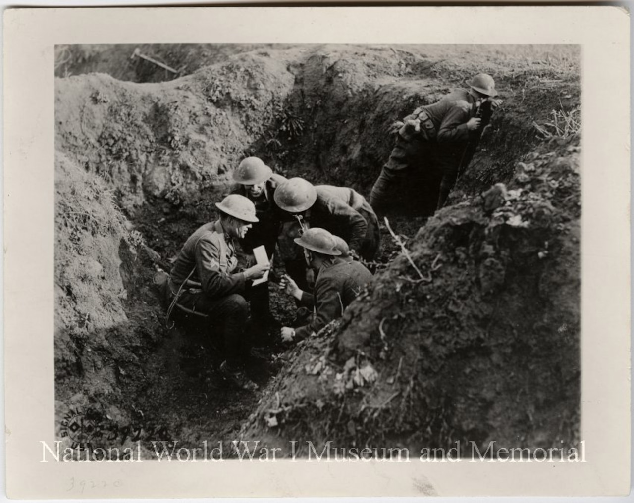 American troops discuss strategy in shell hole in France.