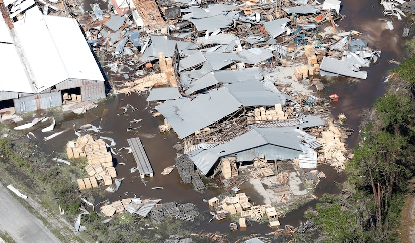 Aerial photo shows warehouses damaged by a hurricane that are surrounded by debris.