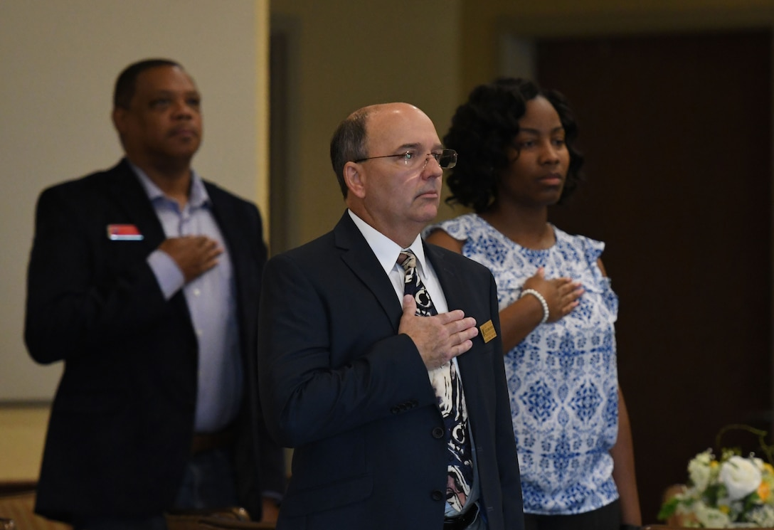 Gary Fulton, Keesler Federal Credit Union northern region director of branch operations, stands during the national anthem at the Biloxi Chamber Morning Call in the Bay Breeze Event Center at Keesler Air Force Base, Mississippi, Oct. 11, 2018. Local business and community leaders attended the event, hosted by the 81st Training Wing, to learn more about the base's mission and its Airmen. (U.S. Air Force photo by Kemberly Groue)