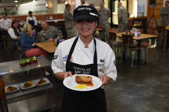 U.S. Air Force Airman 1st Class Michelle Vi Torculas, a food services specialist assigned to the 97th Force Support Squadron, presents the dish she prepared for the 2017 Chopped Chef Challenge, November 28, 2017, at Altus Air Force Base, Okla. The five competitors of the Hangar 97 cooking staff were given a basket containing six random ingredients to create a three-course meal within two hours. Torculas won the region two 2018 Arthur J. Myers Food Service Excellence Award for her hard work in events like this and in her career. (U.S. Air Force photo by Senior Airman Kirby Turbak)