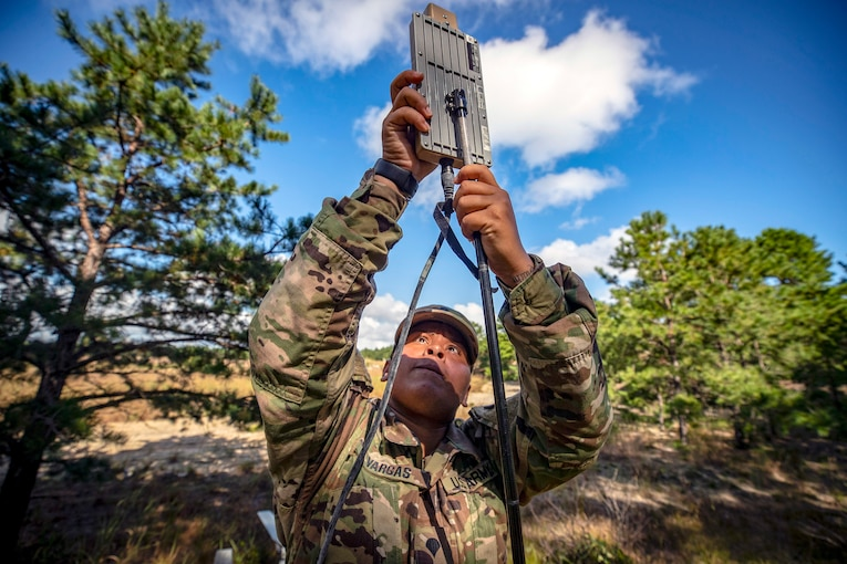A solder places an antenna on a stand in a field.