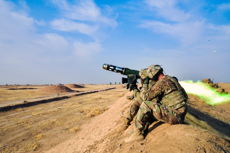 Two soldiers sit on a ridge and fire a large anti-tank missile.