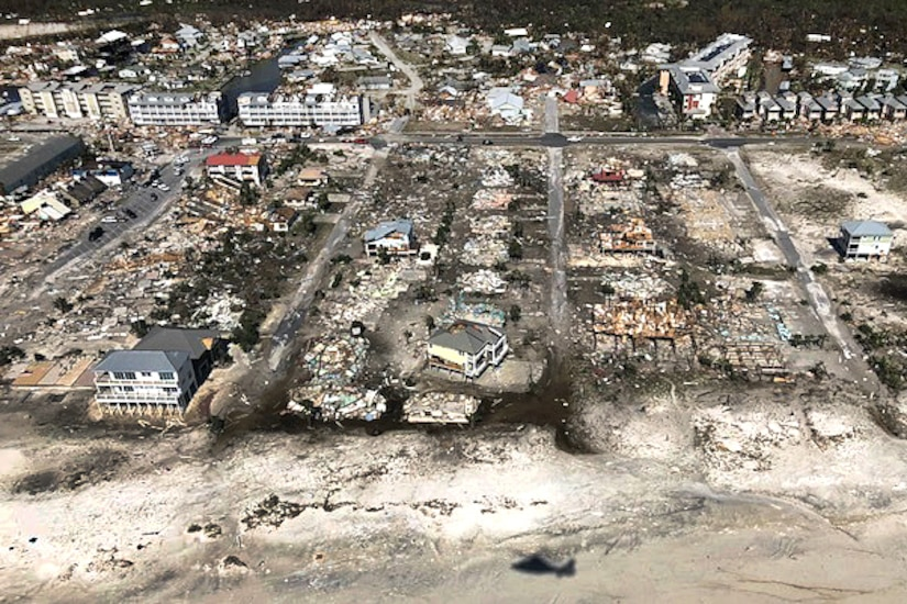Damaged and destroyed homes dot the coastline of a beach, visible from overhead.