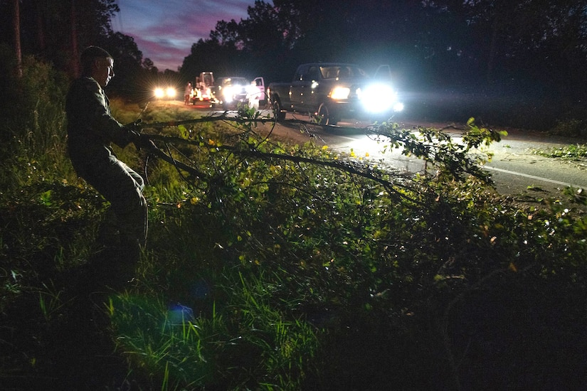 A soldier moves a tree from a highway at night, as vehicles line the roadway.