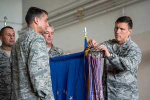 Col. Jeffrey Wilkinson (right), commander of the 123rd Airlift Wing, pins a streamer representing the unit's 17th Air Force Outstanding Unit Award to the wing guidon during a ceremony at the Kentucky Air National Guard Base in Louisville, Ky., Sept. 16, 2018. The award is one of many which contributes to the wing's status as one of the most decorated units in Air Force history. (U.S. Air National Guard photo by Staff Sgt. Joshua Horton)