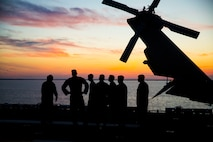 Marines and sailors with the 24th MEU watch the sunset while embarking from Naval Station Norfolk, Virginia, Oct. 2 in preparation of Exercise Trident Juncture 18.
