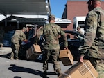 Florida National Guard Soldiers from the 53rd Infantry Brigade Combat Team, 2-124 Charlie Co., Ocala, Fla., load food in to a local citizen's vehicle during Hurricane Michael disaster relief, Panama City, Fla., Oct. 13, 2018.  Soldiers respond in communities throughout the panhandle in conjunction with civilian emergency services.