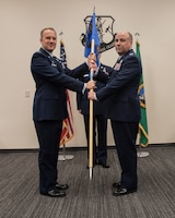 Col. Johan Deutscher, 141st Air Refueling Wing commander, passes the 141st Mission Support Group guidon to Col. David Kimpel, 141st MSG commander, during a change of command ceremony October 13, 2018 at Fairchild Air Force Base, Wash. During the ceremony, a guidon is passed to symbolize the passing of responsibility from one commander to another.(U.S. Air National Guard photo by Tech. Sgt. Michael Lee Brown)