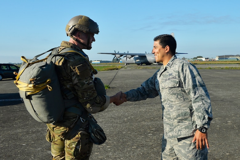 U.S. Air Force Capt. Christian Lora, 424th Air Base Squadron airfield operations flight commander, right, shakes hands with a 435th Air Ground Operations Wing paratrooper on Chievres Air Base, Belgium, Oct. 4, 2018. As a geographically separated unit of the 86th Airlift Wing at Ramstein Air Base, Germany, the 424th ABS conducts airfield support operations for U.S. and NATO forces. (U.S. Air Force photo by Senior Airman Joshua Magbanua)