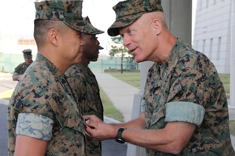 USAG CAMP HUMPHREYS, Republic of Korea – Maj. Gen. Patrick J. Hermesmann (right), commander of U.S. Marine Corps Forces Korea, awards Gunnery Sgt. Hung Tran, MARFORK G-1 administration chief, a Navy and Marine Corps Commendation Medal here, Oct. 4. Tran was awarded the medal for his superior performance at his previous unit, Manpower Management Integration Branch, Manpower Management Division. (U.S. Marine Corps photo by Staff Sgt. Anthony Kirby/Released)