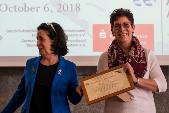 Elke Sittel, 86th Airlift Wing Host Nation official, smiles as she holds her recognition plaque during the 35th Annual German-American Day celebration in Kaiserslautern, Germany, Oct. 6, 2018. Sittel was recognized for her accomplishments in regards to trans-Atlantic relations. (U.S. Air Force photo by Staff Sgt. Jonathan Bass)