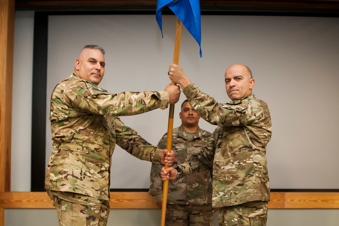 Lt. Col. Michael LoForti, 920th Operations Group commander, passes the unit's guidon to the new 920th Operations Support Squadron Maj. Ricardo Montana during a change of command ceremony at Patrick Air Force Base, Florida, Oct. 13, 2018. During the ceremony the squadron's Airmen sent off Lt. Col. Scott Nichols, the previous 920th OSS, to the 301st Rescue Squadron. (U.S. Air Force photo by Tech. Sgt. Jared Trimarchi)
