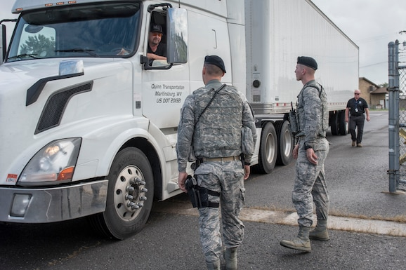 Airman 1st Class Braden Stutzman and Airman 1st Class Greg Tenney, 167th Airlift Wing Security Forces, greet a driver at a gate into the 167th Airlift Wing, Sept. 13. The tractor and trailer contained FEMA emergency relief supplies which were staged at the Martinsburg, W.Va. air base in anticipation of flooding from Hurricane Florence. (U.S. Air National Guard photo by Senior Master Sgt. Emily Beightol-Deyerle)