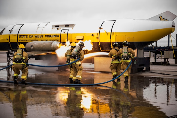 Firefighters from the 167th Airlift Wing extinguish an engine fire on the mobile aircraft fire simulator provided by West Virginia University State Fire Academy during annual Federal Aviation Administration Part 139 Live Fire Training at Martinsburg, W.Va., Oct. 13-14, 2018. (U.S. Air National Guard photo by Staff Sgt. Timothy Sencindiver)