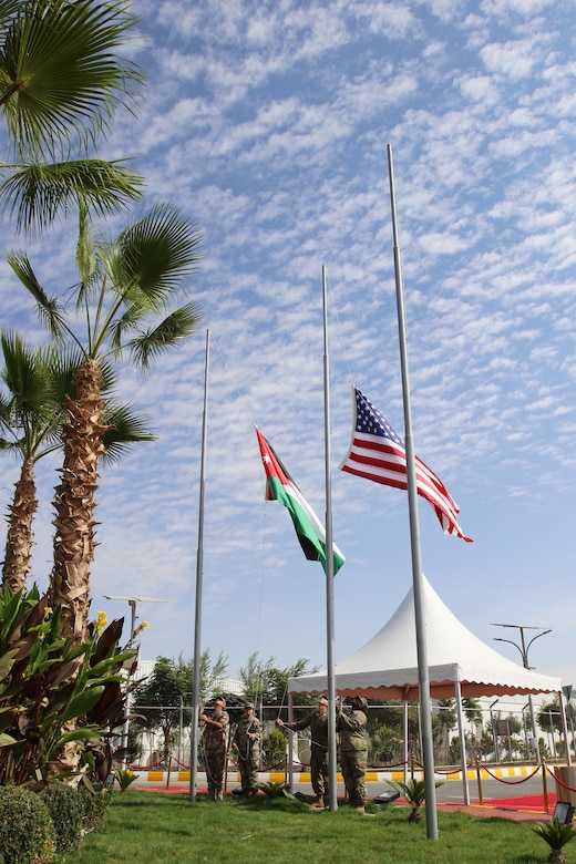 A flag-raising detail hoists the Jordan and U.S. flags during a dedication ceremony for an expansion of the Jordan Armed Forces Joint Training Center on Oct. 10, 2018. The new center provides U.S. military service members with modern living quarters and office space while they train with JAF soldiers on combat and border security skills.