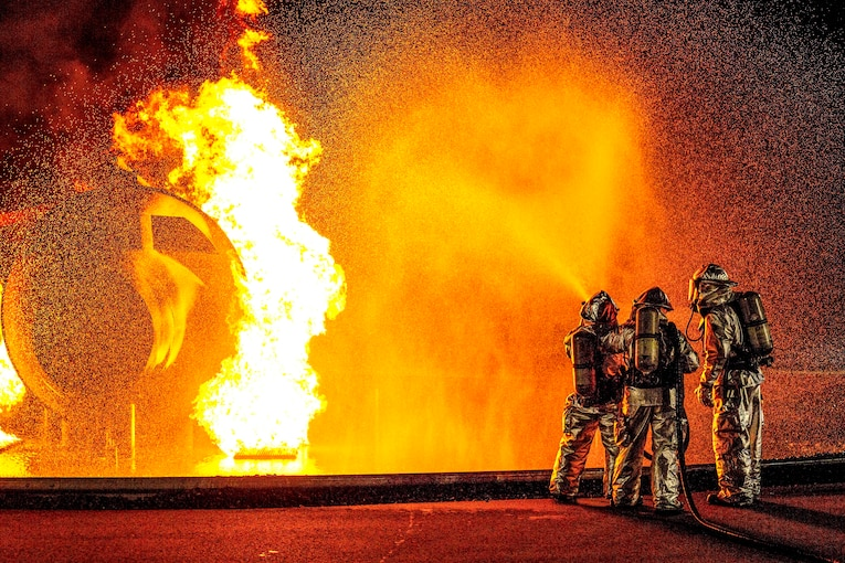 Three firefighters spray water on an aircraft engulfed in flames, illuminating the night sky  with orange light.