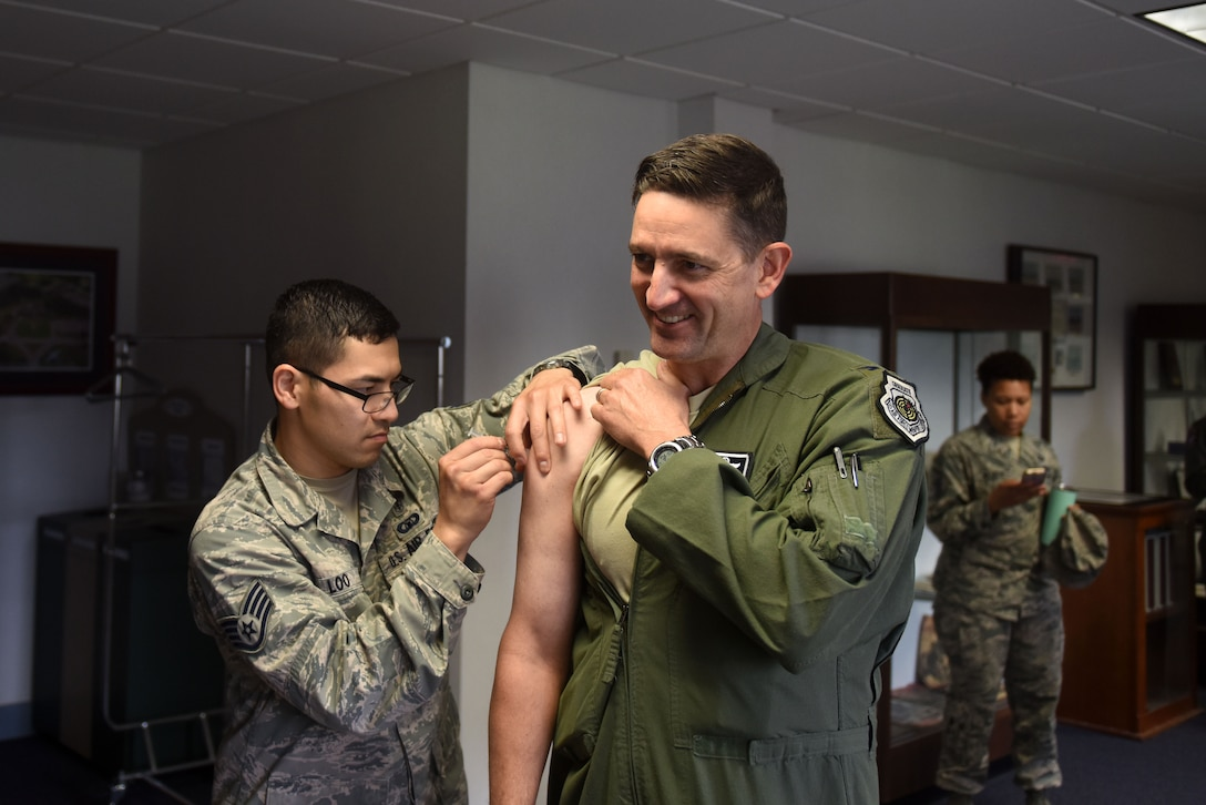 A man with dark hair wearing a flight suit receives a flu shot from a man with dark hair and glasses wearing the Airman Battle Uniform.