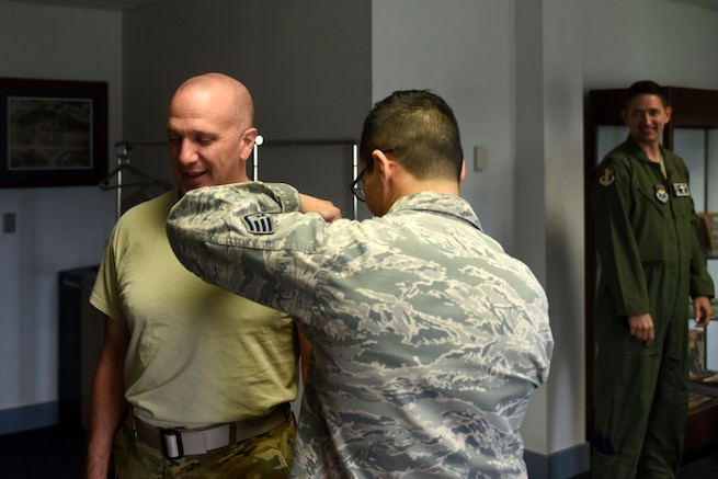 A man wearing a sand-colored t-shirt receives a shot from a man with dark hair and glasses wearing the Airman Battle Uniform.