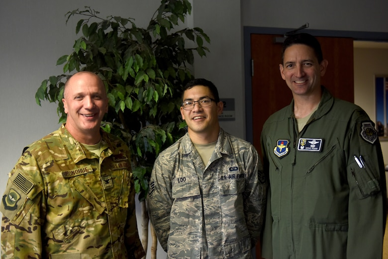 Three men stand smiling at the camera. The farthest left is smiling and wearing the Operational Camouflage Patter uniform, the middle is a man with dark hair and glasses wearing the Airman Battle Uniform and the far right man is wearing a green flight suit.