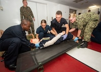 Sailors aboard the hospital ship USNS Comfort conduct stretcher bearer training during a mass casualty drill.