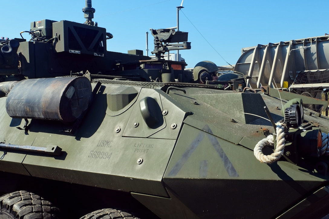 A U.S. Marine Light Armored Vehicle crewman drives onto the loading ramp of a Landing Craft Air Cushion at Mile Hammock Bay, Camp Lejeune, North Carolina, Oct. 5, 2018 during Type Commander Amphibious Training. TCAT allows the 24th Marine Expeditionary Unit, their subordinate units, and the U.S. Navy's Iwo Jima Amphibious Ready Group to rehearse ship to shore maneuver and expeditionary command and control prior to exercise Trident Juncture 2018. The goal of TCAT is to increase unit and individual proficiency during amphibious operations. The LAVs are with 2nd Light Armored Reconnaissance Battalion, 24th Marine Expeditionary Unit.  (U.S. Marine Corps photo by Gunnery Sgt. Robert Durham/released)