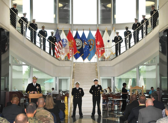 DLA Land and Maritime Commander Rear Admiral John Palmer, left, addresses the audience as officers and sailors stand in formation along the staircase in background.