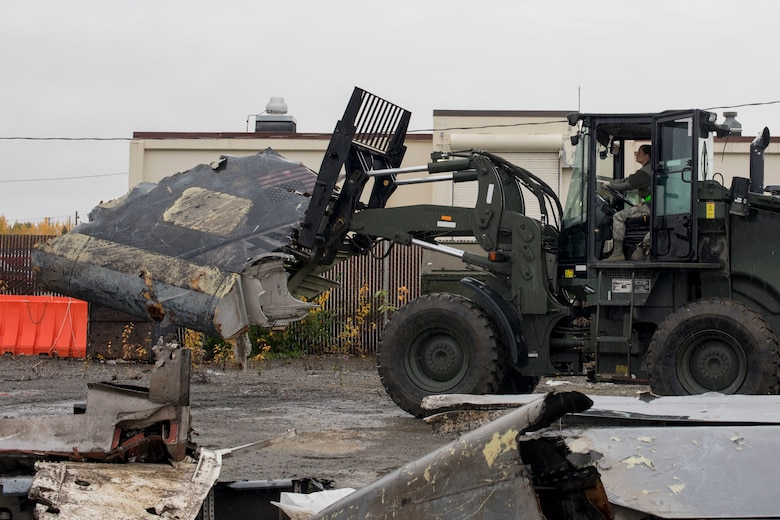U.S. Air Force Airman 1st Class Pamela Proteau, a 773d Logistics Readiness Squadron vehicle operator, picks up part of a wing using a 10k all-terrain forklift to remove wreckage debris at Joint Base Elmendorf-Richardson, Alaska, Sept. 28, 2018. Proteau was part of a large wreckage disposal team whose mission was to remove debris from the fatal crash of the Sitka 43 C-17 Globemaster III that had been stored at JBER since 2010. After multiple shipments, the 'Sitka 43' wreckage is finding a new purpose at the Air Force Safety Center (AFSEC) Crash Lab at Kirtland Air Force Base, N.M.