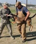 """Cadet Royse (left) """"catching"""" a Military Working Dog on a bite sleeve under the supervision of Rene Torres (left), an MWD Breeding Program Training Instructor."""