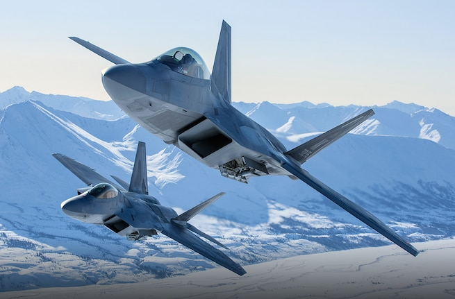 A pair of F-22 Raptors from Joint Base Elmendorf-Richardson, Alaska, fly above snow capped mountains. The Air Force Reserve Command has opportunities to fly this aircraft and many more. Read a step-by-step on what it takes to become a pilot in the Reserve. (Courtesy photo)