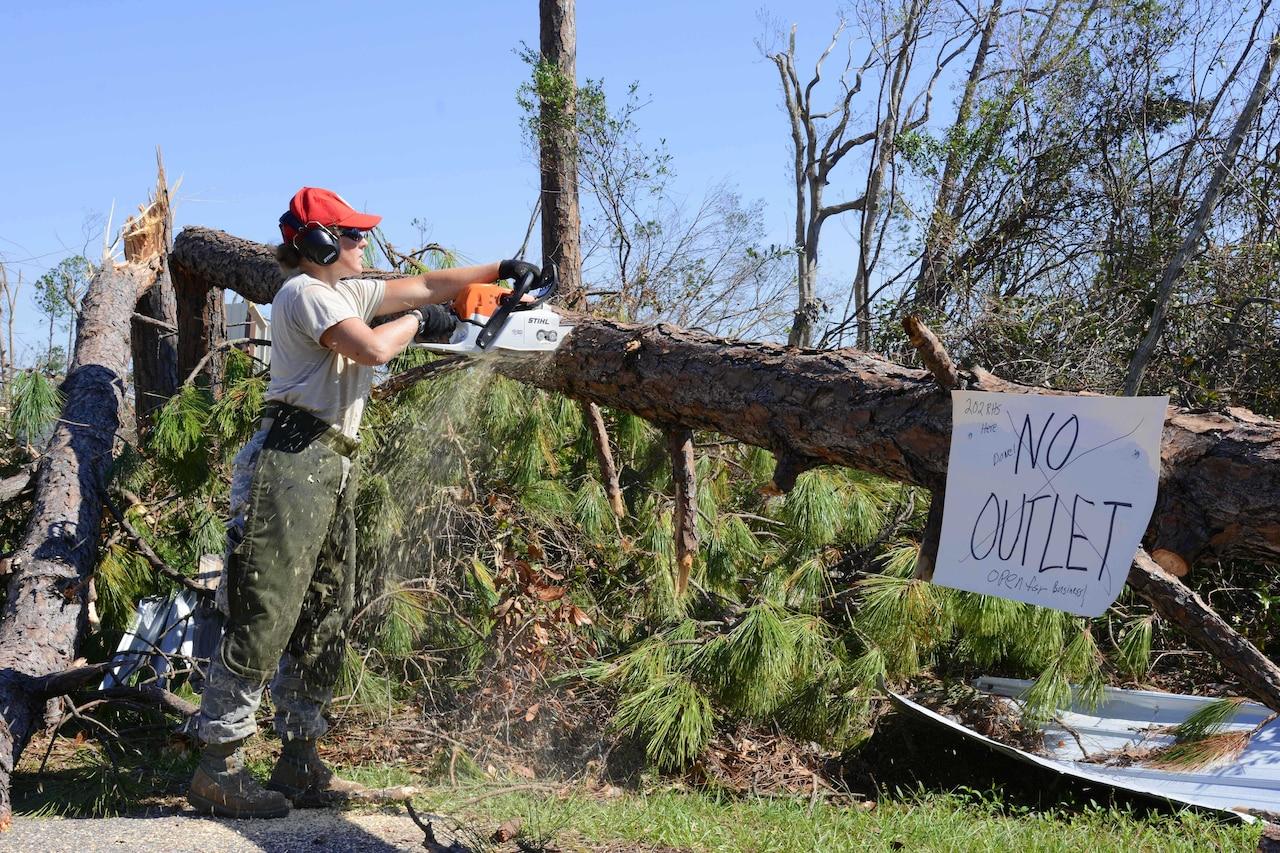 An Air Force engineer saws through a felled tree using a chainsaw.