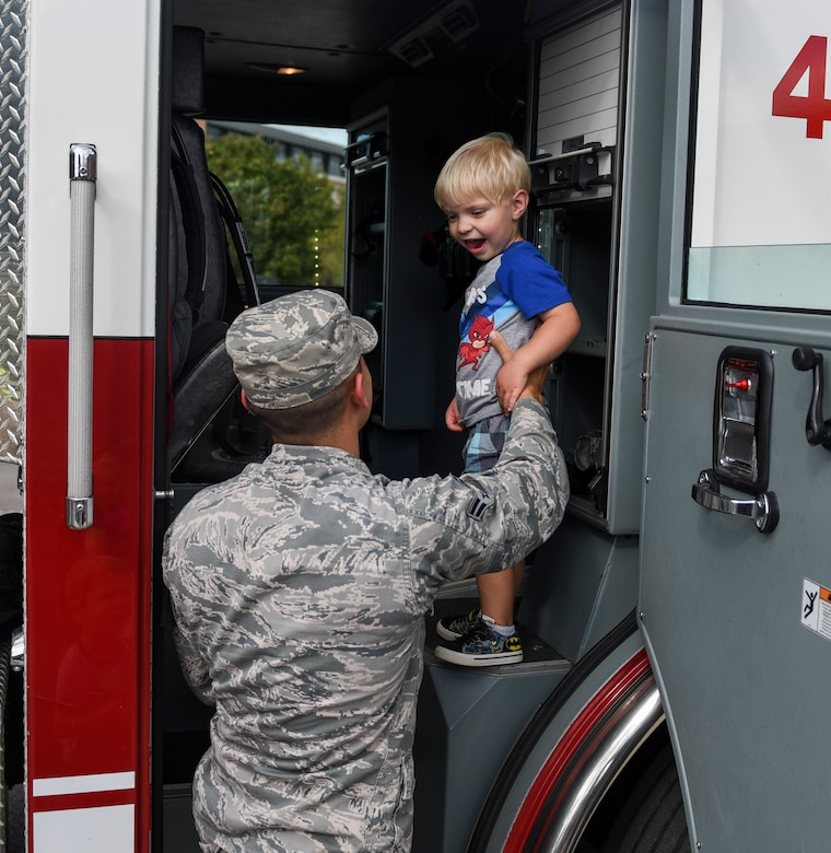 Airman 1st Class Brian Rios, 375th Civil Engineer Squadron firefighter, lifts a child into a fire truck during a visit to the Scott Air Force Base Child Development Center as part of 2018 National Fire Prevention Week, Oct. 9. Throughout the week the fire department visited the Child Development Centers, Scott Elementary School, the Scott Youth Center, hosted a puppet show at the base library, and held an open house and Fall Festival at Fire Station 2 on base. (U.S. Air Force photo by Airman 1st Class Chad Gorecki)