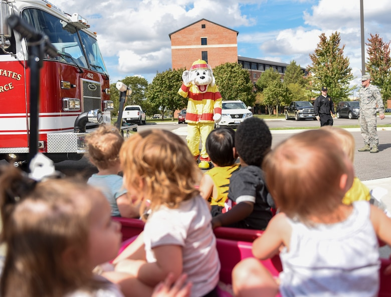 Sparky the fire dog waves to children during a visit to the Scott Air Force Base Child Development Center as part of 2018 National Fire Prevention Week, Oct. 9. Throughout the week the fire department visited the Child Development Centers, Scott Elementary School, the Scott Youth Center, hosted a puppet show at the base library, and held an open house and Fall Festival at Fire Station 2 on base. (U.S. Air Force photo by Airman 1st Class Chad Gorecki)