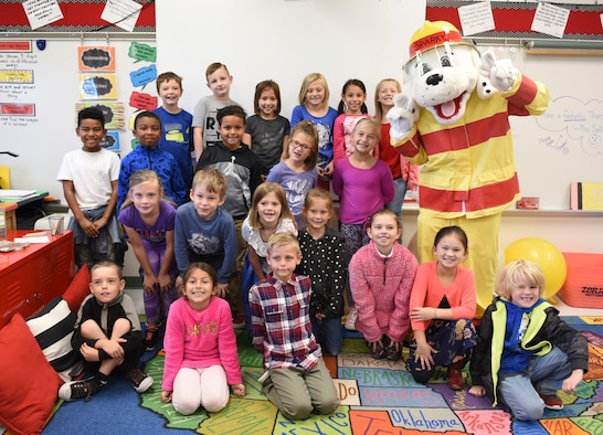 "Students at the Scott Air Force Base Elementary School pose for a group picture with Sparky the fire dog during a visit by the 375th Civil Engineer Squadron Fire Department as part of 2018 National Fire Prevention Week, Oct. 11. This year, the Scott fire department approached the week with a ""Look, Listen, Learn"" theme to ensure the community is aware of hazards and show what they can provide. (U.S. Air Force photo by Airman 1st Class Chad Gorecki)"