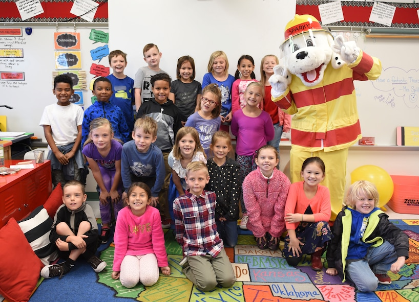 """Students at the Scott Air Force Base Elementary School pose for a group picture with Sparky the fire dog during a visit by the 375th Civil Engineer Squadron Fire Department as part of 2018 National Fire Prevention Week, Oct. 11. This year, the Scott fire department approached the week with a """"Look, Listen, Learn"""" theme to ensure the community is aware of hazards and show what they can provide. (U.S. Air Force photo by Airman 1st Class Chad Gorecki)"""