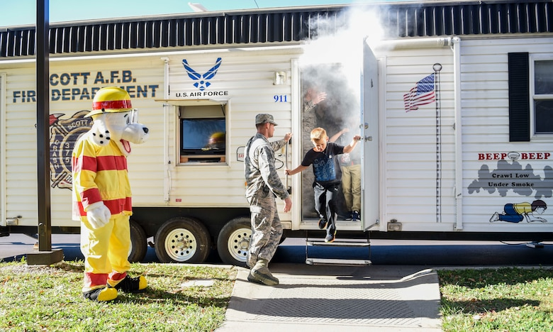 "Children from the Scott Air Force Base Youth Center exit the 375th Civil Engineer ""smoker"" during a presentation as part of 2018 National Fire Prevention Week, Oct. 11. The smoker simulates how quickly a room can fill up with smoke and allows the opportunity to practice getting low and finding an exit during a fire. (U.S. Air Force photo by Airman 1st Class Chad Gorecki)"