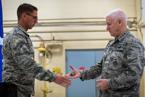 U.S. Air Force Lt. Gen. L. Scott Rice, right, the director of the Air National Guard, coins Airman 1st Class Jason Grabiec, a photojournalism specialist with the 182nd Airlift Wing, during a visit to the 182nd Airlift Wing in Peoria, Ill., Oct. 14, 2018.
