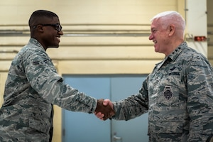 U.S. Air Force Lt. Gen. L. Scott Rice, right, the director of the Air National Guard, coins Airman 1st Class Herbert Houston IV, a security forces specialist with the 182nd Security Forces Squadron, during a visit to the 182nd Airlift Wing in Peoria, Ill., Oct. 14, 2018.