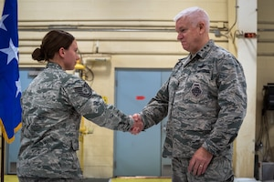 U.S. Air Force Lt. Gen. L. Scott Rice, the director of the Air National Guard, coins Tech. Sgt. Samantha Copeland, a fuels craftsman with the 182nd Logistics Readiness Squadron, during a visit to the 182nd Airlift Wing in Peoria, Ill., Oct. 14, 2018.